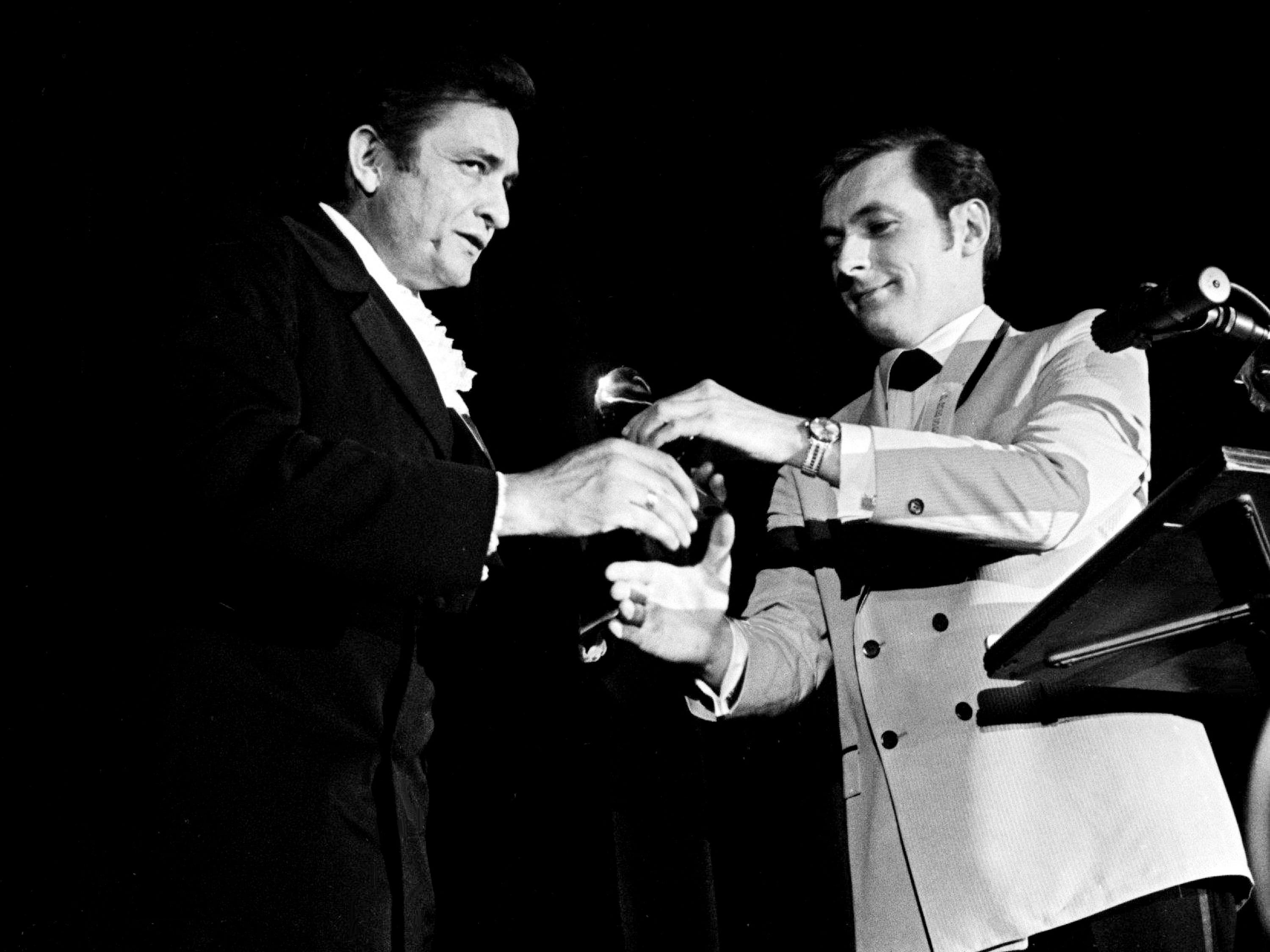 "Country music star Johnny Cash, left, is receiving one of his two awards during the 11th annual Grammy Award show at the National Guard Armory in Nashville March 12, 1969. He won Best Country Male Performance and the Album Notes for his ""Folsom Prison Blues."""