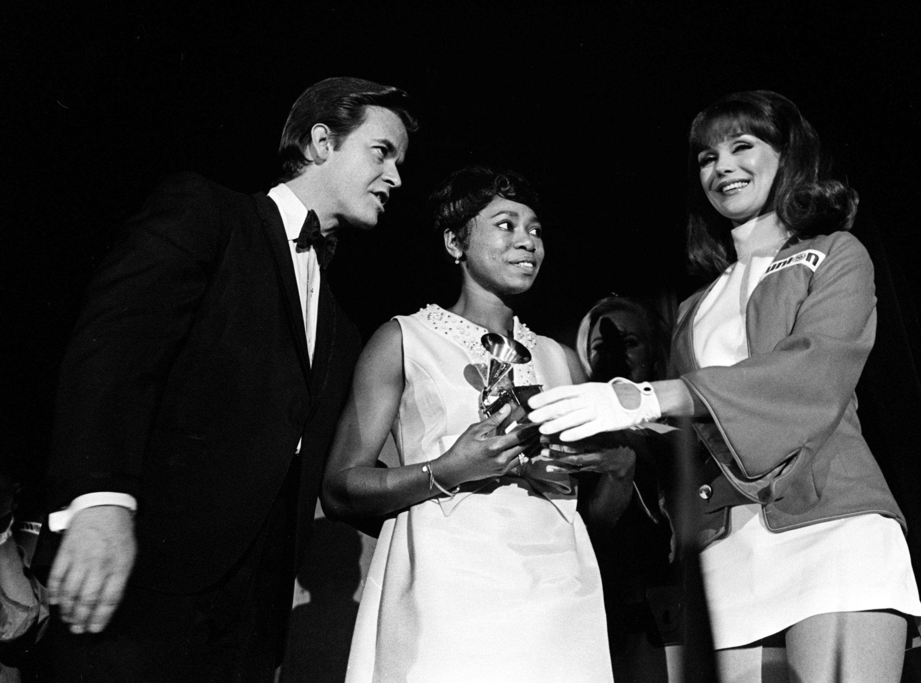 "Zelma Redding, center, is accepting one of two awards for her late husband, Otis Redding, during the 11th annual Grammy Award show at the National Guard Armory in Nashville March 12, 1969. The singer, who was killed in a plane crash last year, won the Best Rhythm and Blues Male Performance and Best Rhythm and Blue Song awards for ""Dock Of The Bay."" Master of ceremonies Dick Clark, left, looks on."