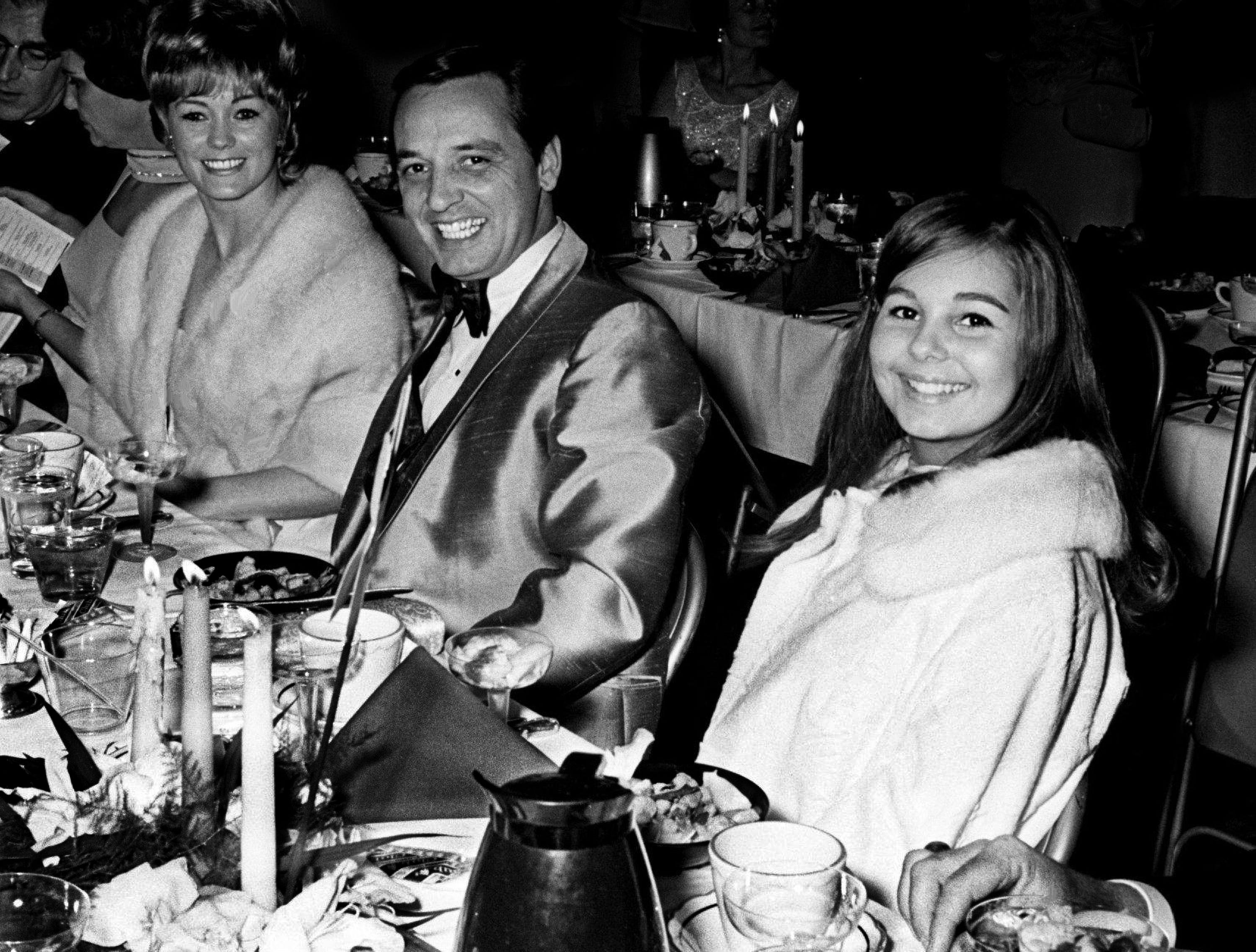 The Tennessean publisher Amon Carter Evans, center, and daughter Janet Evans, right, along with other family members, are enjoying the 11th annual Grammy Awards celebration at the National Guard Armory in Nashville March 12, 1969.