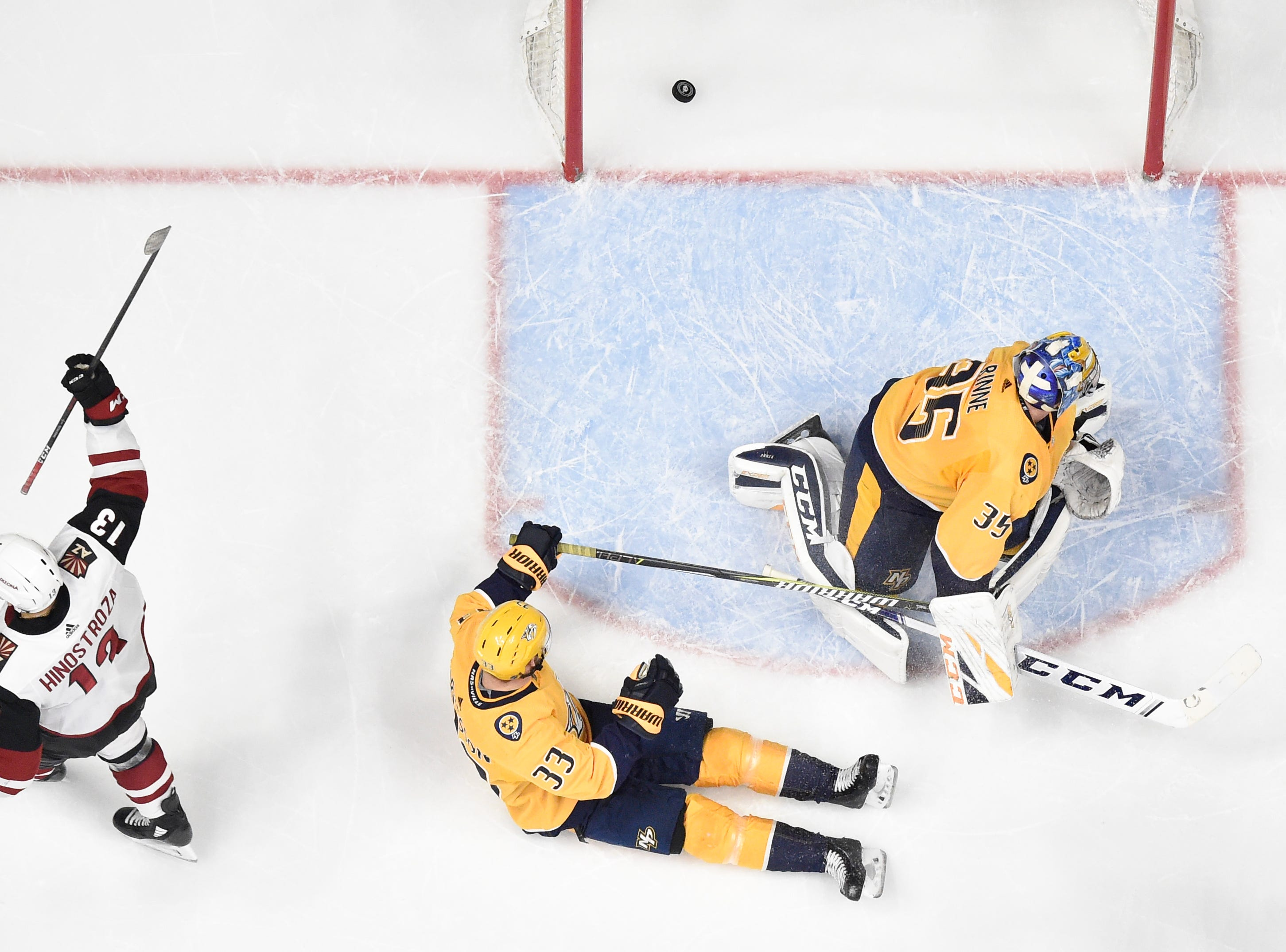 Arizona Coyotes center Vinnie Hinostroza (13) scores past Nashville Predators goaltender Pekka Rinne (35) and right wing Viktor Arvidsson (33) during the first period at Bridgestone Arena in Nashville, Tenn., Tuesday, Feb. 5, 2019.