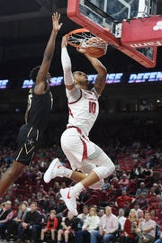 Arkansas forward Daniel Gafford, right, dunks the ball over Vanderbilt defender Clevon Brown, left, during the first half of an NCAA college basketball game, Tuesday, Feb. 5, 2019 in Fayetteville, Ark.