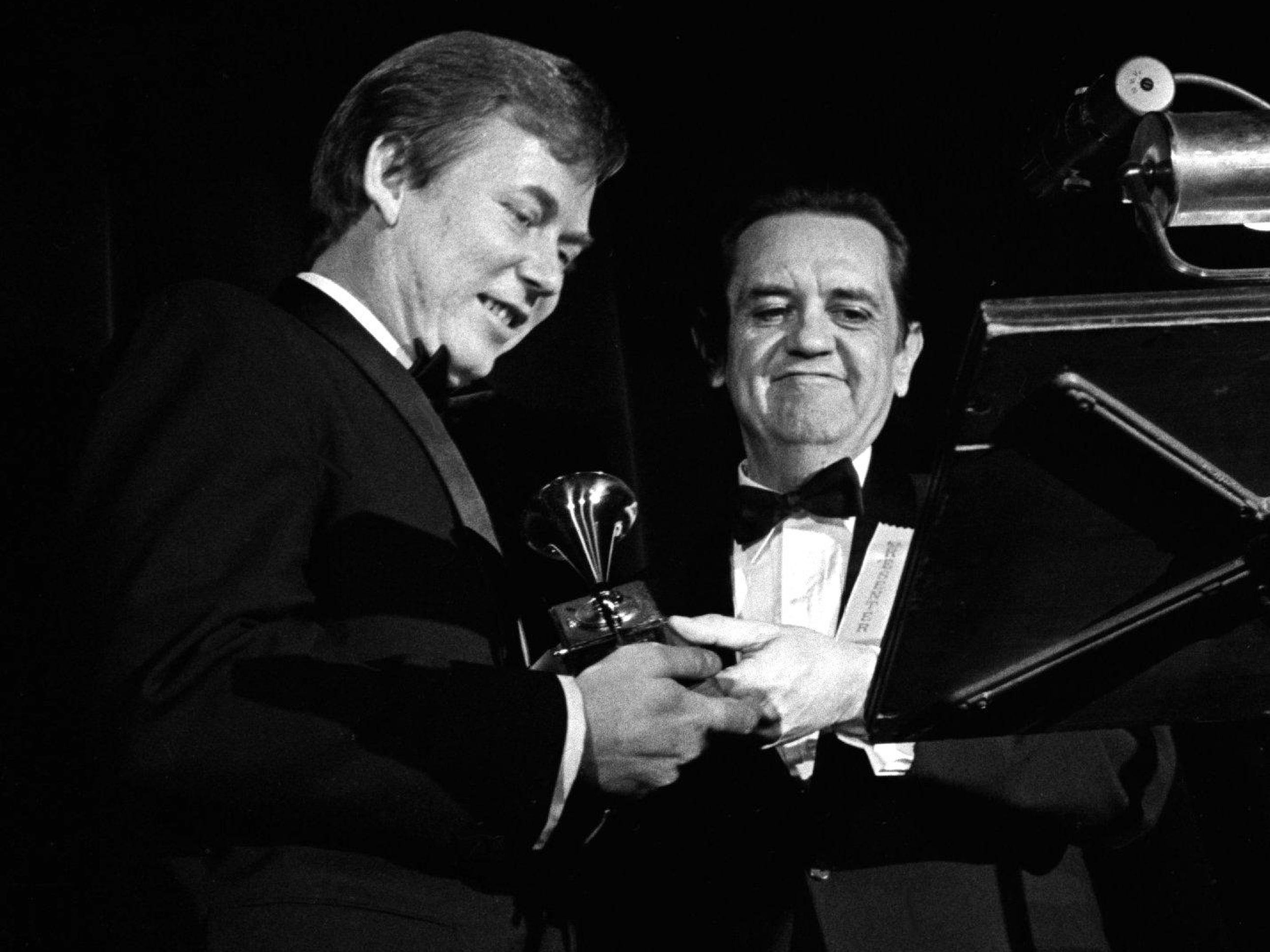 "Bobby Russell, left, receives one of his two Grammy awards from presenter Merle Travis during the 11th annual Grammy Award show at the National Guard Armory in Nashville March 12, 1969. Russell won for writing the Song of the Year and the Best Country Song, both for ""Little Green Apples."""