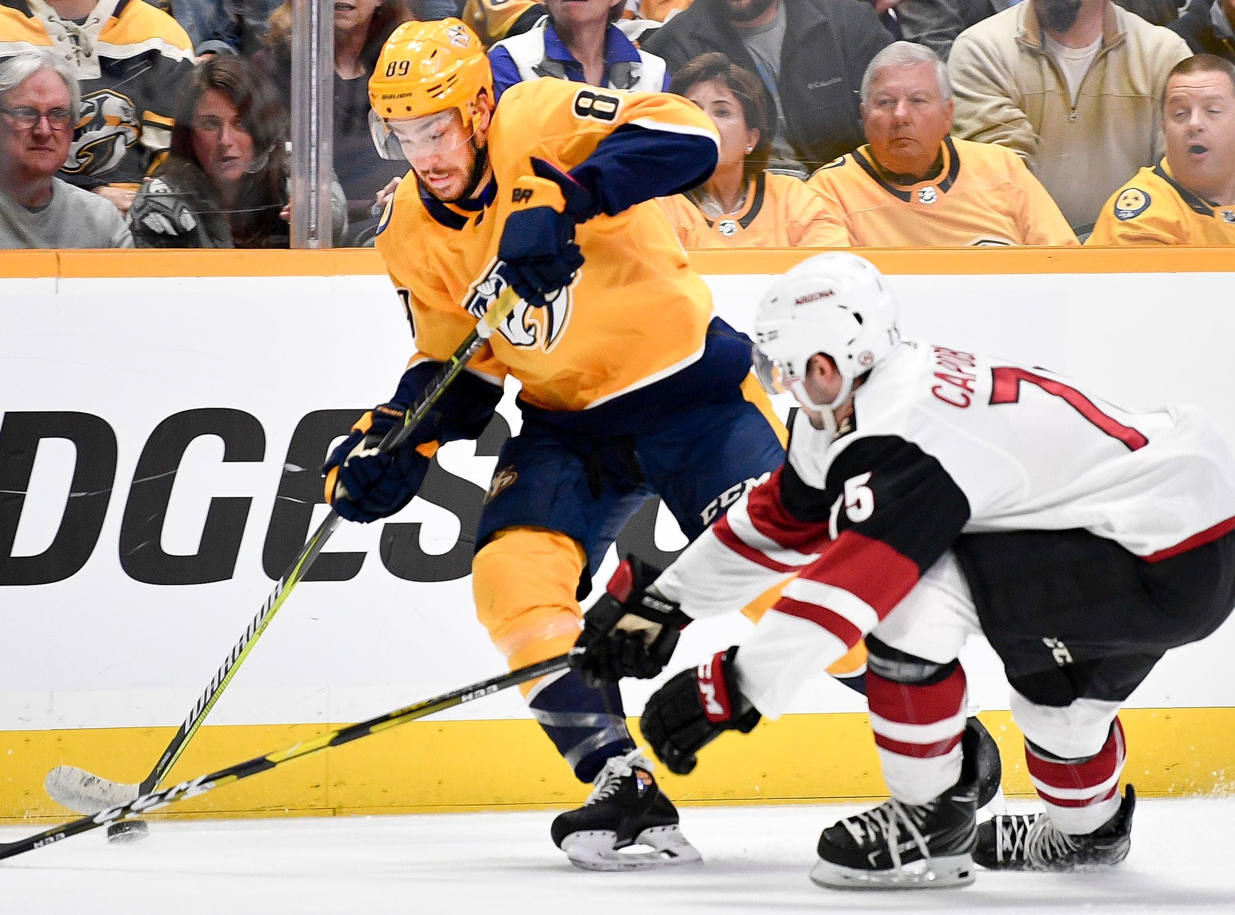 Nashville Predators center Frederick Gaudreau (89) chases the puck with Arizona Coyotes defenseman Kyle Capobianco (75) during the first period at Bridgestone Arena in Nashville, Tenn., Tuesday, Feb. 5, 2019.
