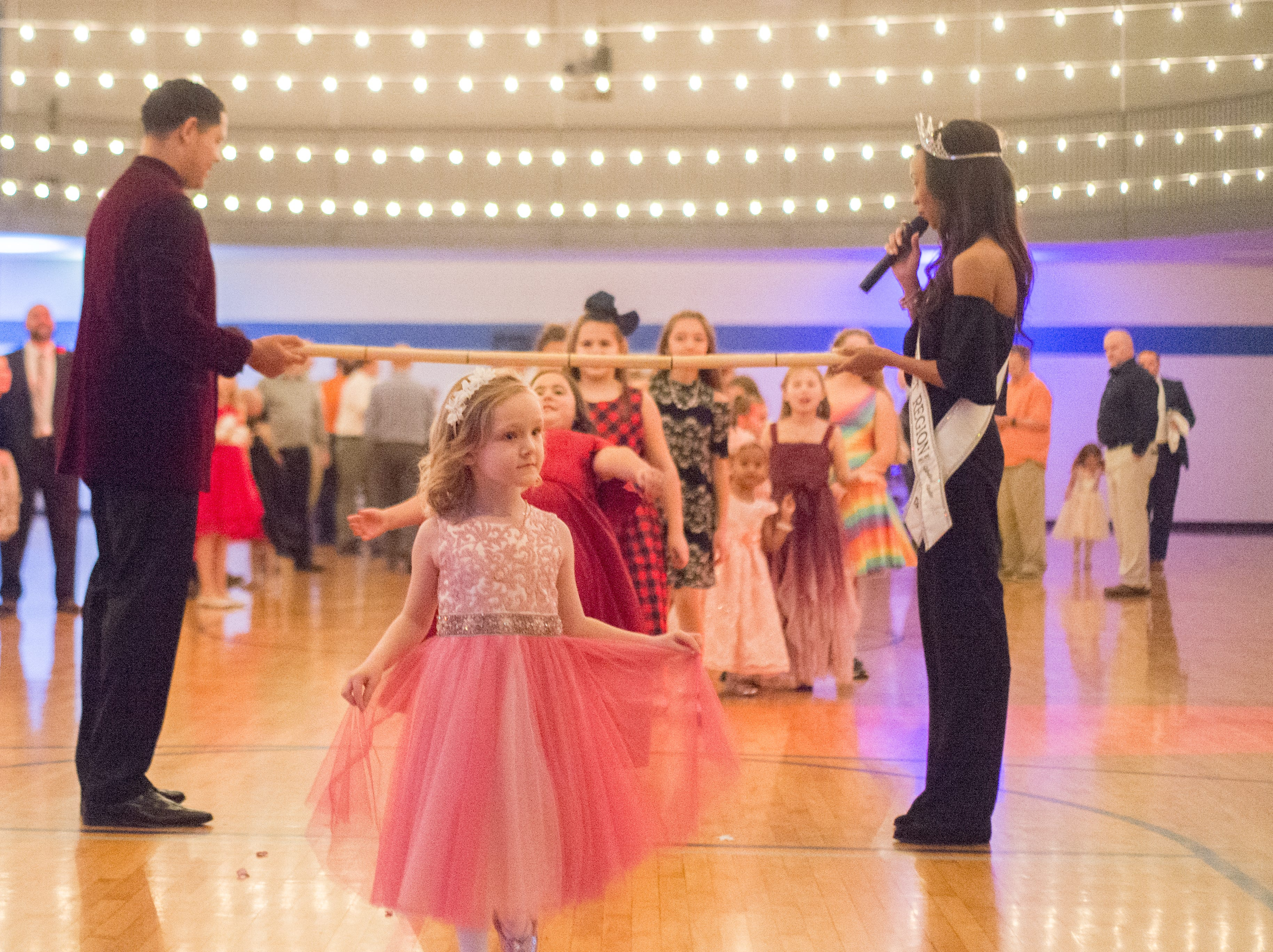Attendees see how low they can go during a Daddy Daughter Dance held at Delmas Long Community Center on Saturday, Feb. 2, 2019.
