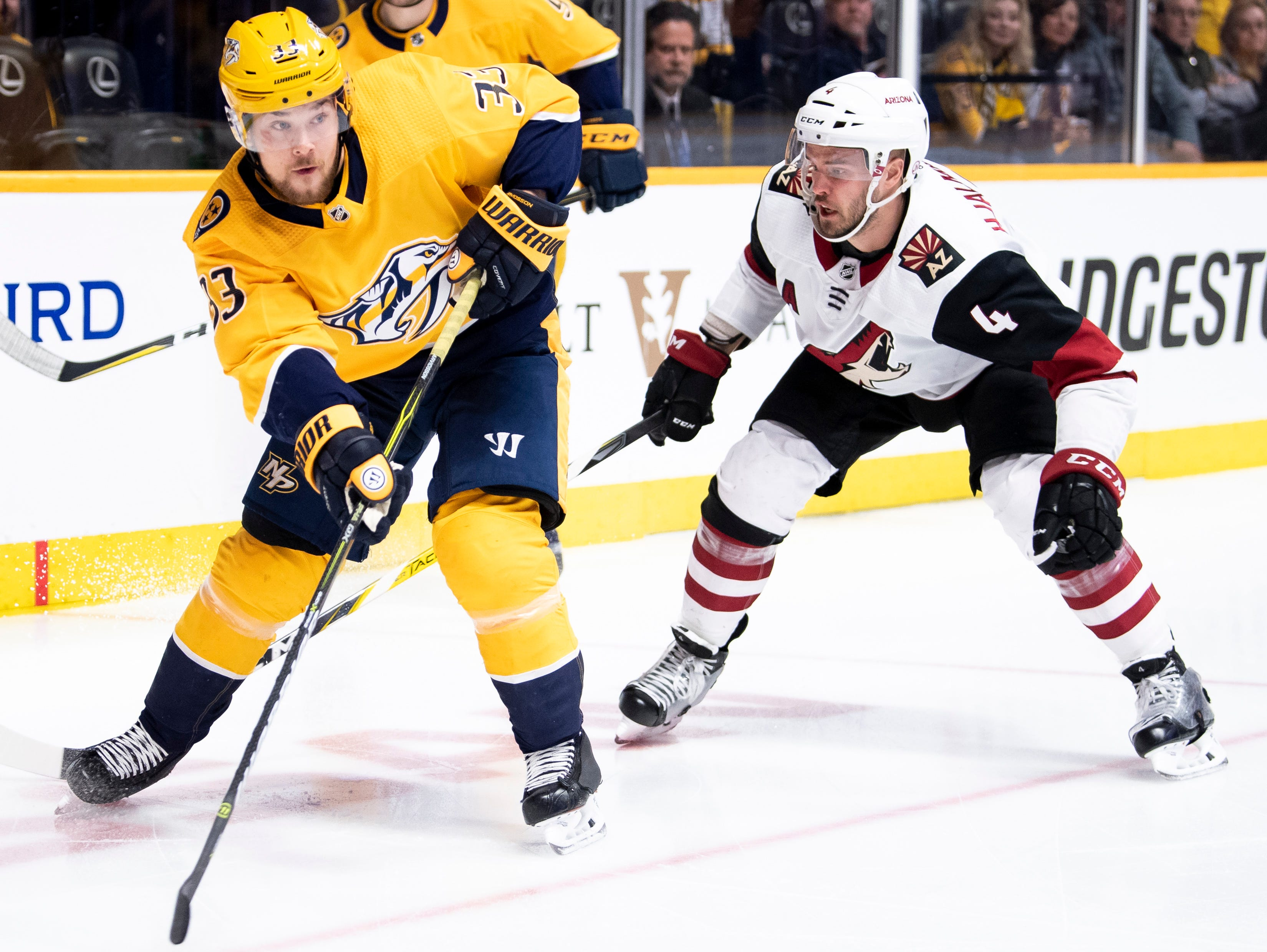 Nashville Predators right wing Viktor Arvidsson (33) maneuvers past Arizona Coyotes defenseman Niklas Hjalmarsson (4) during the first period at Bridgestone Arena in Nashville, Tenn., Tuesday, Feb. 5, 2019.