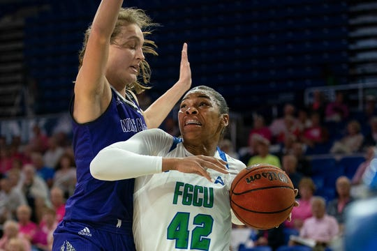 FGCU's Tytionia Adderly, right, goes up for the basket against North Alabama's Brittany Panetti, during FGCU's home game at Alico Arena in Fort Myers.