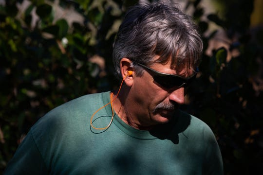 Lee Haddox does landscape work while wearing noise-canceling earplugs in Naples on Wednesday, Feb. 6, 2019.