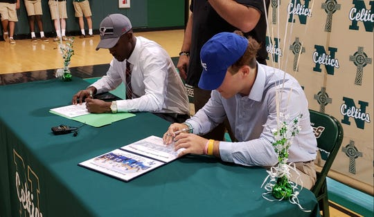St. John Neumann football players Nyre Handy (left) and Jensen Jones sign letters of intent to play in college on National Signing Day on Wednesday. Jones is headed to Air Force, while Handy will play at Florida Tech.