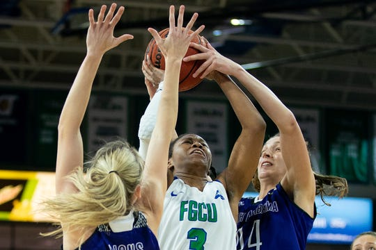 FGCU's Keri Jewett-Giles, center, goes up for the basket against North Alabama's defense during FGCU's home game at Alico Arena in Fort Myers.