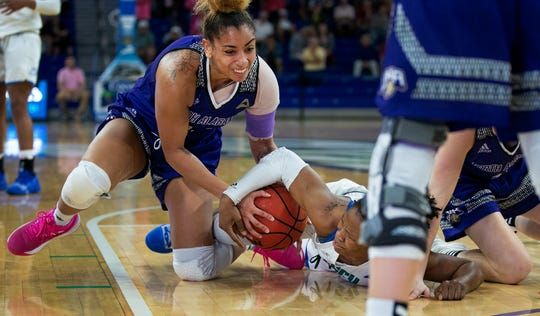 FGCU's Keri Jewett-Giles, right, and North Alabama's defense Kenysha Coulson, left, fight for the possession during FGCU's home game at Alico Arena in Fort Myers.