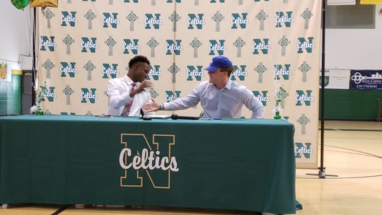 St. John Neumann football players Nyre Handy (left) and Jensen Jones celebrate signing letters of intent to play in college on National Signing Day on Wednesday.  Jones is headed to Air Force, while Handy will play at Florida Tech.