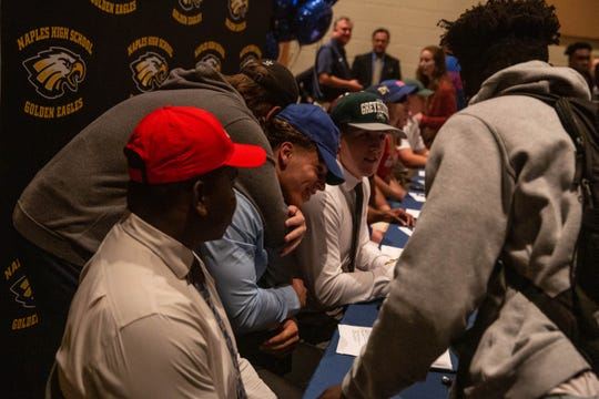 Marc Viechec recieves a hug from a friend after signing a letter of intent to play football at University of West Florida                  on National Signing Day in Naples on February 6, 2019.