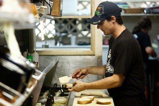 John Midkiff prepares lunch orders in the Larry's Lunch Box kitchen in Naples on Wednesday, July 30, 2014.