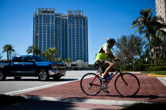 A biker rides along Pelican Bay Boulevard past the construction site of Mystique, a luxury high-rise development in Naples, on Wednesday, Feb. 6, 2019.