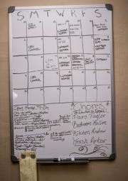 A calendar on the wall of the Hull house diving up chores and organizing community events and meetings.
