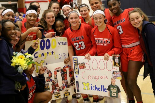 Michelle Sidor (23), is surrounded by here Saddle River Day teammates after becoming the fourth girl in New Jersey high school basketball history to score 3,000 points.