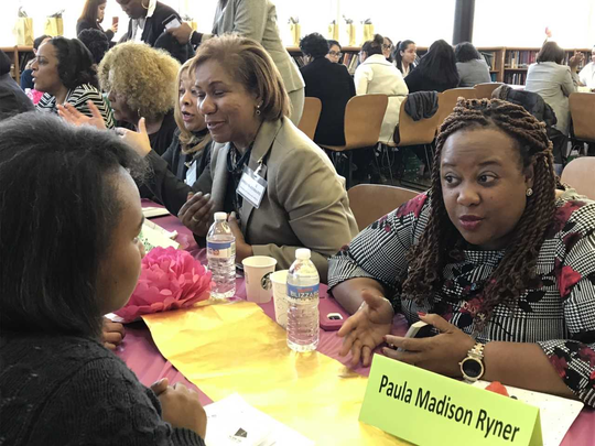 Paula Madison Ryner, president of the Bergen/Passaic Chapter of the National Coalition of 100 Black Women, visits with Paterson  girls about career opportunities.