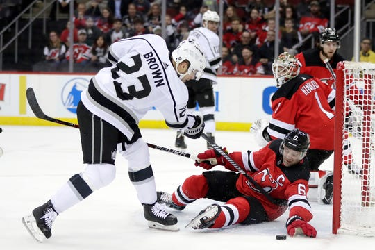 New Jersey Devils defenseman Andy Greene (6) reaches to help make a save as Los Angeles Kings right wing Dustin Brown (23) attacks during the first period of an NHL hockey game Tuesday, Feb. 5, 2019, in Newark, N.J.