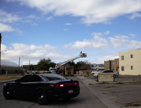 A Las Cruces Police Department vehicle blocks off Parkview Drive on Wednesday, Feb. 6, 2019, as a fire crew maneuvers a truck ladder after successfully extinguishing a blaze in a nearby apartment complex.