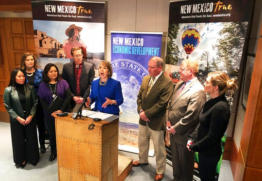 New Mexico Gov. Michelle Lujan Grisham, center, offers her endorsement of a bill to create an outdoor recreation office on Tuesday, Feb. 5, 2019, in Santa Fe, N.M. The new division of state government would promote outdoor activities, guide infrastructure investments and oversee a trust to ensure children from low-income families have access to the state's natural wonders. The governor was accompanied state legislators and Cabinet secretaries.