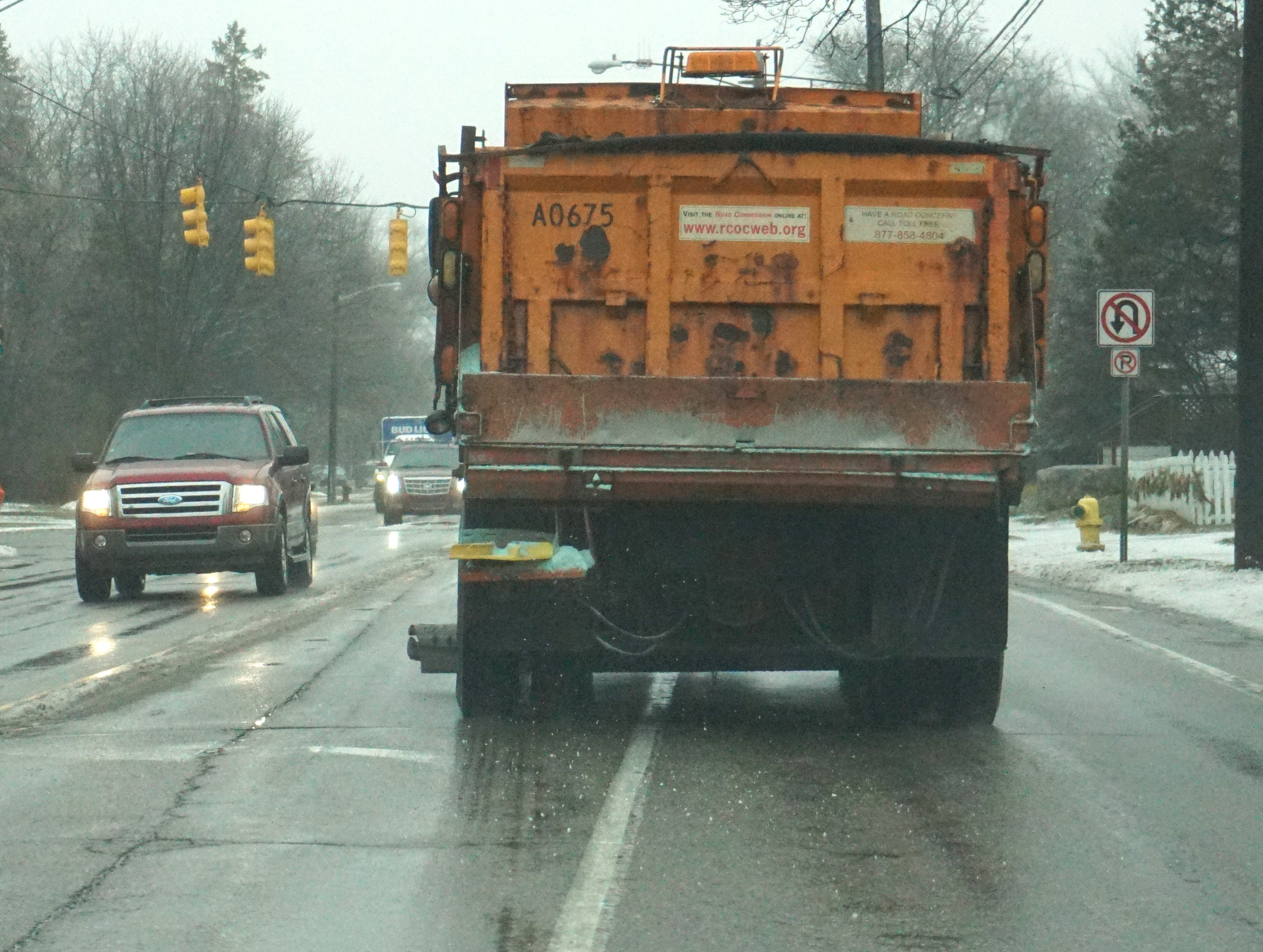 A Road Commission of Oakland County plow truck puts down some salt near downtown Birmingham on Wednesday afternoon - as icy and slushy road surfaces continue.