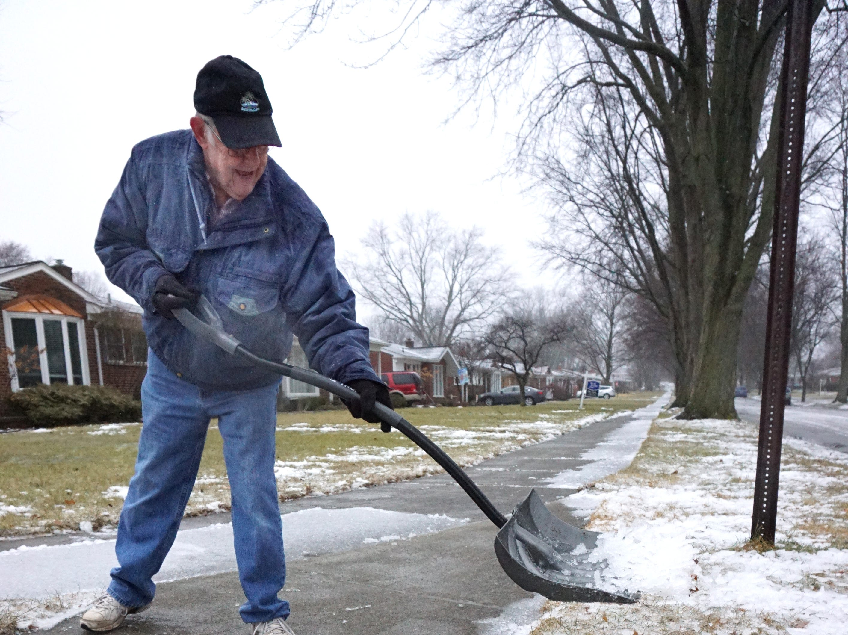 84 year-old Farmington Hills resident Bill Matheny tosses some icy mixture off his Frederick Street home on Wednesday afternoon. Matheny said he comes out for a bit, does some shoveling and then goes back inside for a rest.