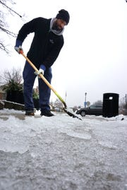 Northville Square employee Troy Manus works last week on scraping away some of the accumulated ice in front of the West Main Street mall. Schools across the region are closed again today due to weather.