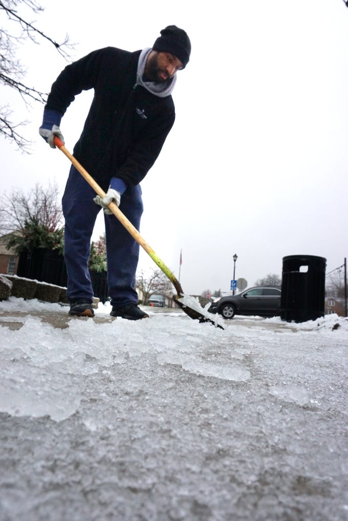 Northville Square employee Troy Manus works on scraping away some of the accumulated ice in front of the West Main Street mall on Wednesday morning.