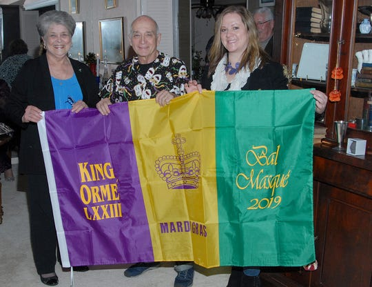 King Orme LXXIII, Donald Richard, receives the official Bal Masque flag from Marguerite Fontenot, left, and Pam Harmon.