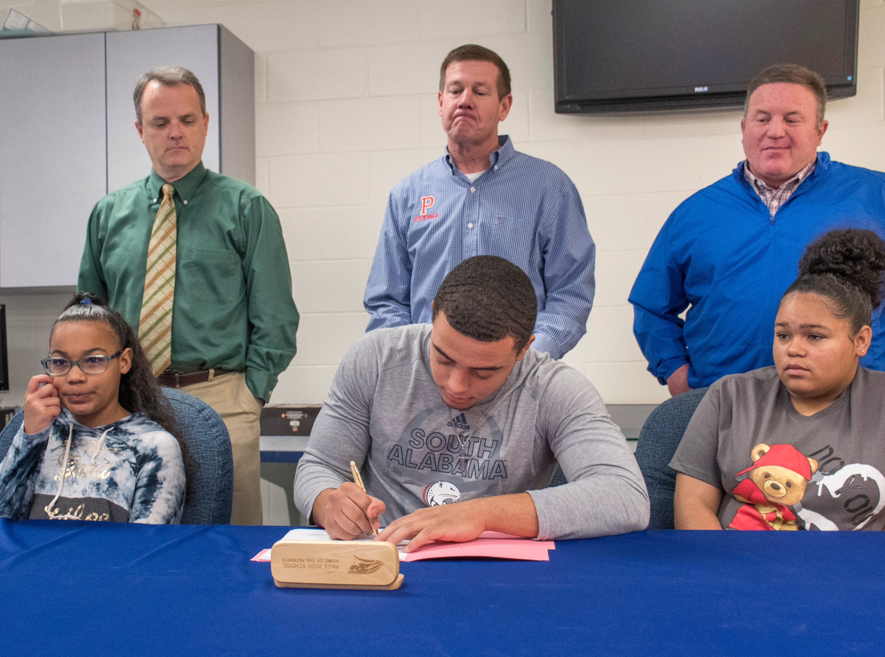 Damean Bivins signs his letter of commitment to play football at the University of South Alabama during a ceremony at Pace High School on Wednesday, February 6, 2019.