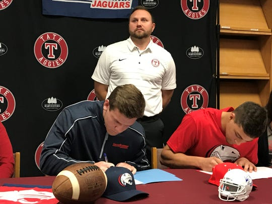 Tate High's Hunter Riggan (left) and Patrick Palmer sign with South Alabama football while head coach Jay Lindsey lets the moment sink in.