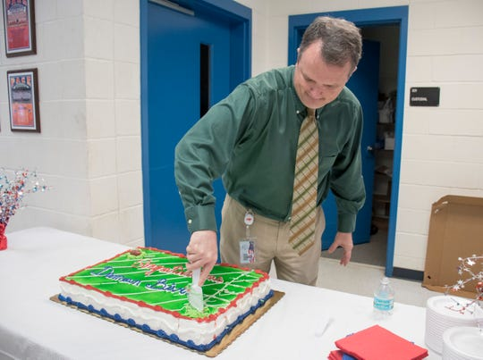 Principal Stephen Shell cuts a cake for Damean Bivins after he signed his letter of commitment to play football at the University of South Alabama during a ceremony at Pace High School on Wednesday, February 6, 2019.