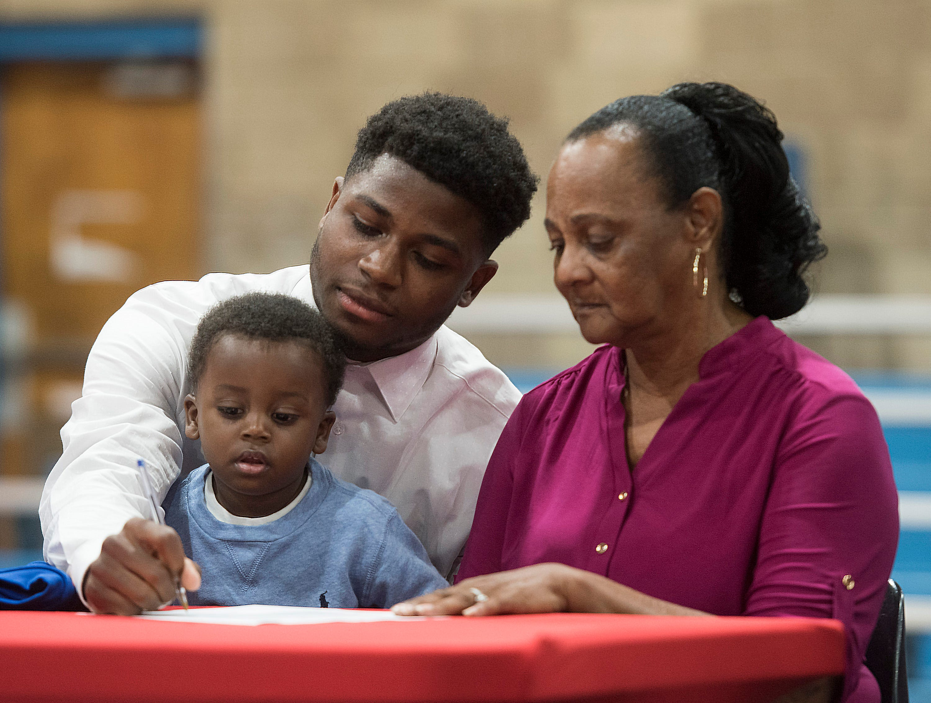 Pine Forest High School's Anwar Lewis commits to Hutchinson Community College in Kansas, on National Signing Day on Wednesday Feb.6, 2019, while his family looks on.