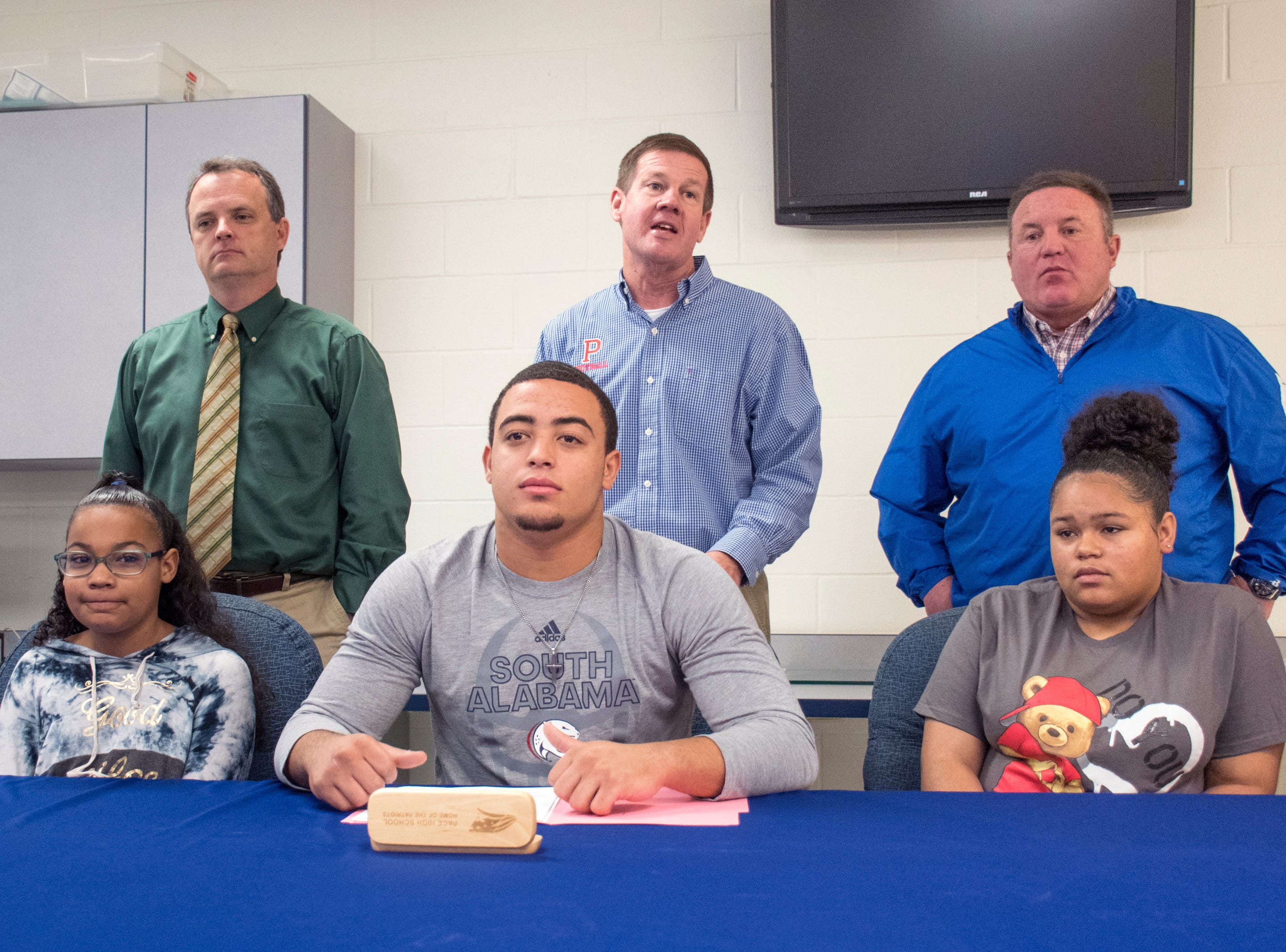 Coach Kent Smith, top center, talks about Damean Bivins before he signs his letter of commitment to play football at the University of South Alabama during a ceremony at Pace High School on Wednesday, February 6, 2019.