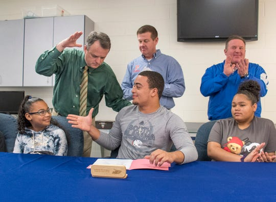 Principal Stephen Shell, top left, congratulates Damean Bivins after he signs his letter of commitment to play football at the University of South Alabama during a ceremony at Pace High School on Wednesday, February 6, 2019.