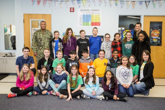At left, Capt. Kertreck Brooks, commanding officer of the Naval Education and Training Professional Development Center, and Command Master Chief Gregory Prichard, far right, visit Beulah Elementary School students Jan. 25 to thank them for the personal letters they wrote to recruits going through Navy basic training at Great Lakes, Illinois.