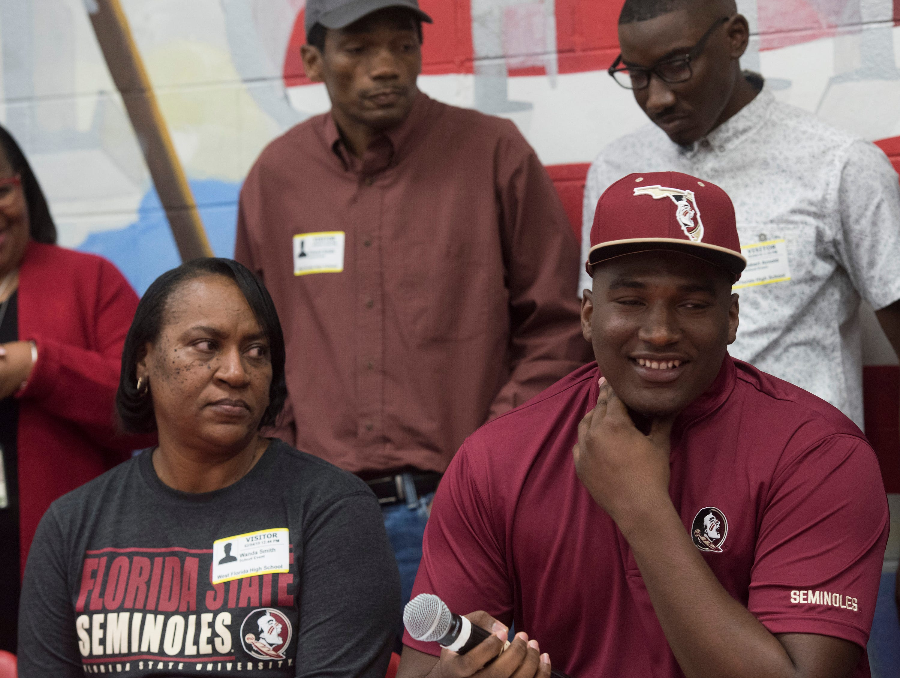West Florida High School's Darius Washington commits to Florida State University on National Signing Day, while his family looks on Wednesday Feb. 6, 2019.
