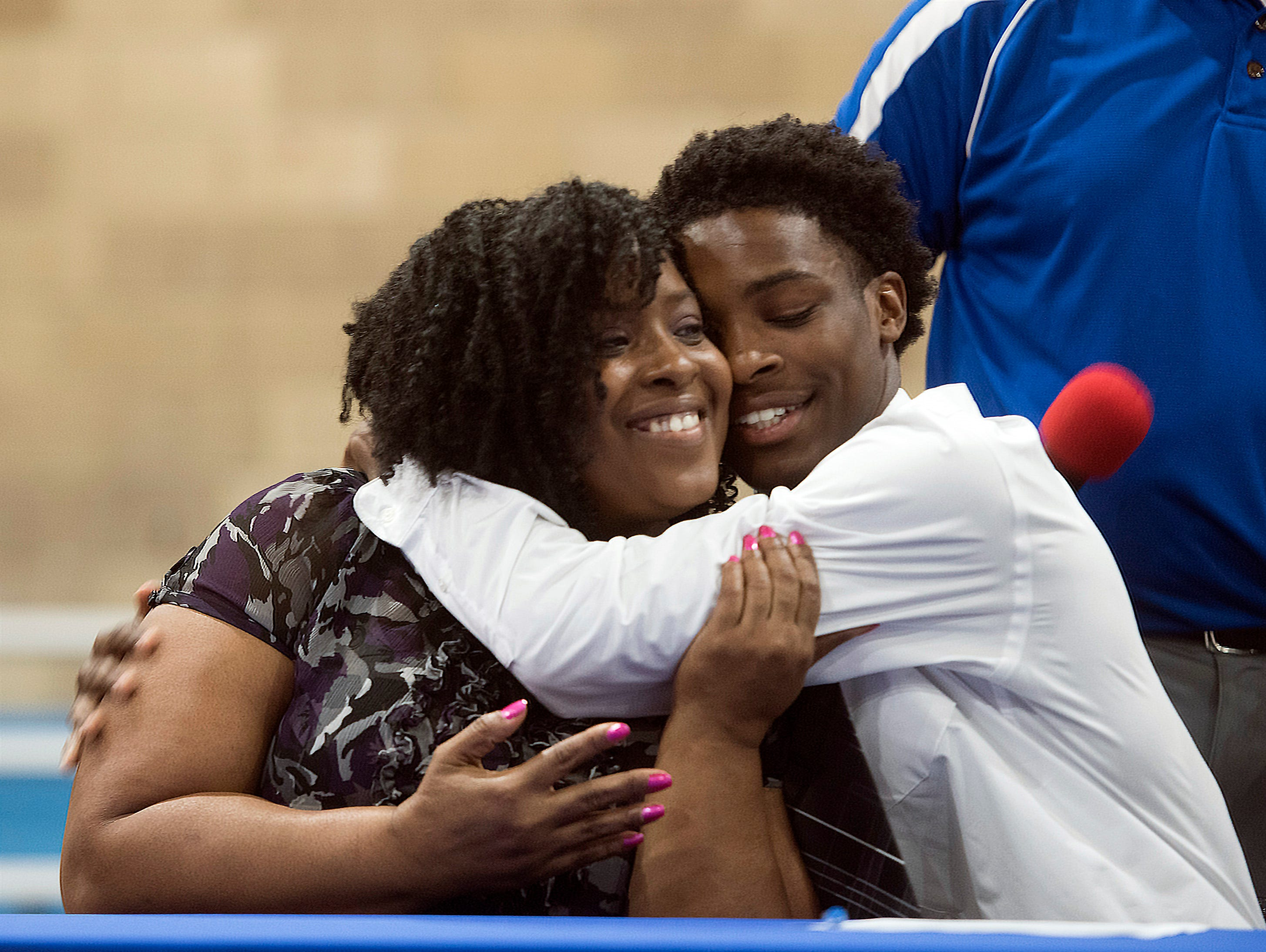 Pine Forest High School's Devon Witherspoon  celebrates with his mom after he commits to Hutchinson Community College in Kansas, on National Signing Day on Wednesday Feb.6, 2019,
