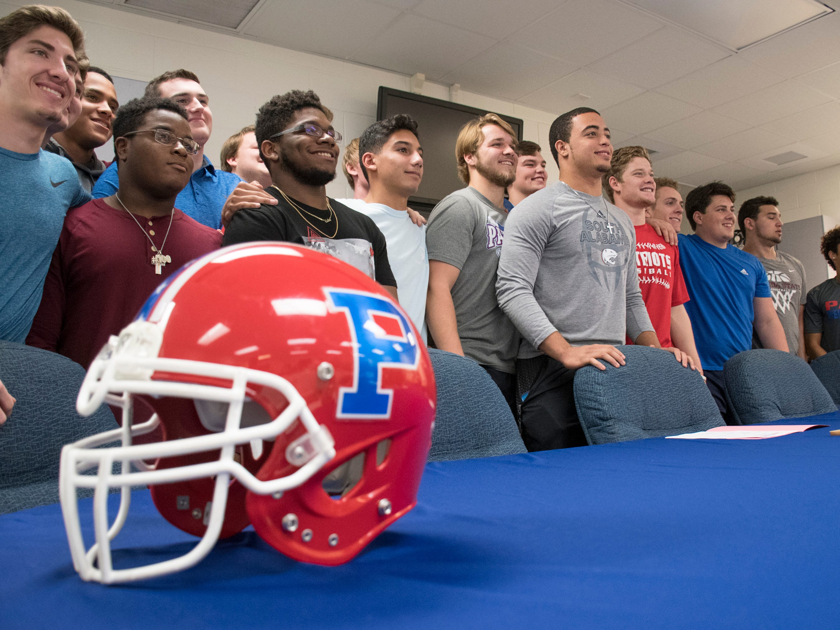 Damean Bivins, center, poses with his senior teammates after he signs his letter of commitment to play football at the University of South Alabama during a ceremony at Pace High School on Wednesday, February 6, 2019.