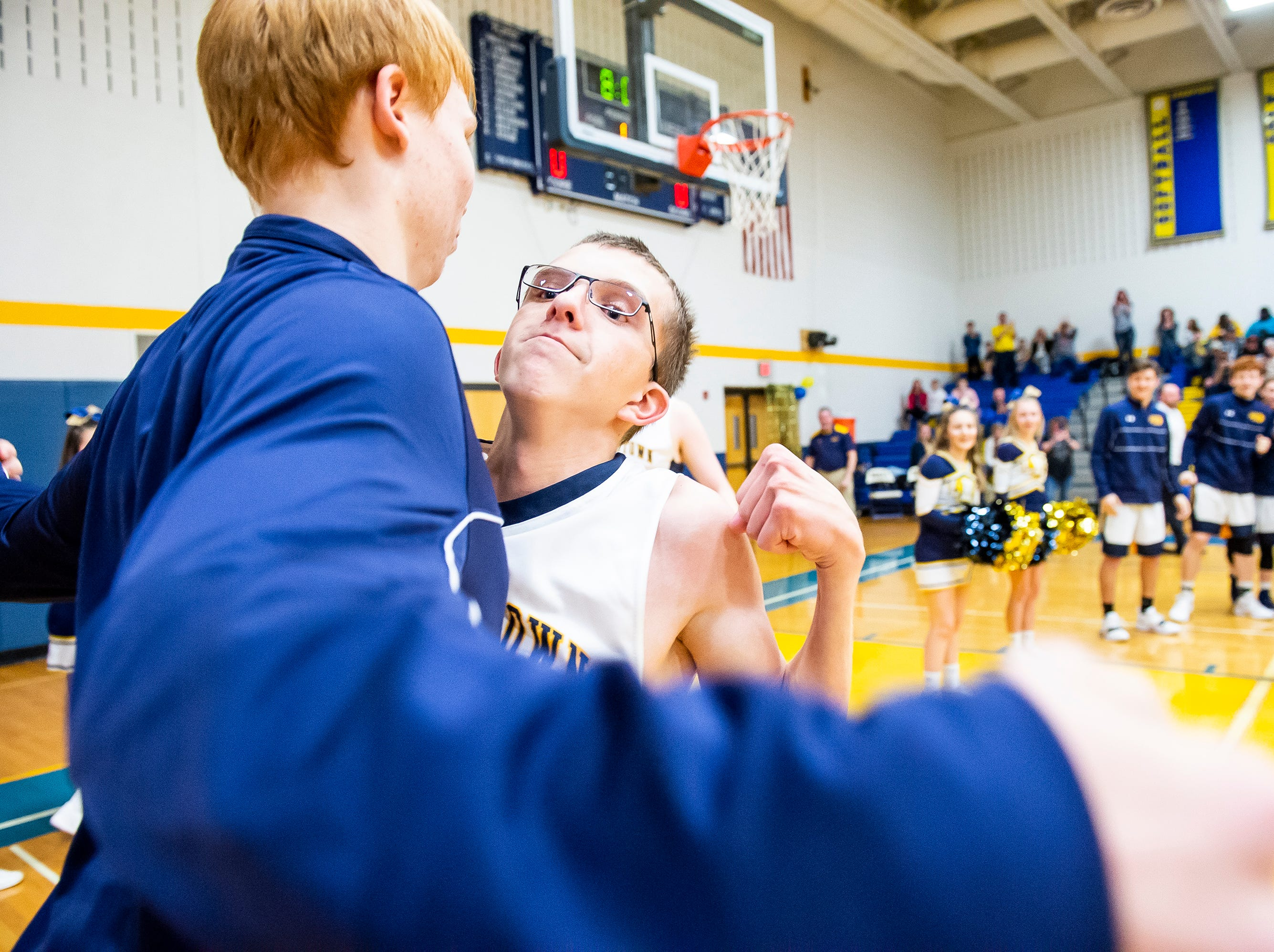 Littlestown's Ben Blankenship chest bumps teammate Daniel Gazmen as he is introduced during the starting lineups prior to a game against Biglerville Tuesday, February 5, 2019. Blankenship, one of the team's managers, started in the number 23 jersey and scored the first points of the game as the Bolts won 54-46 on senior night.