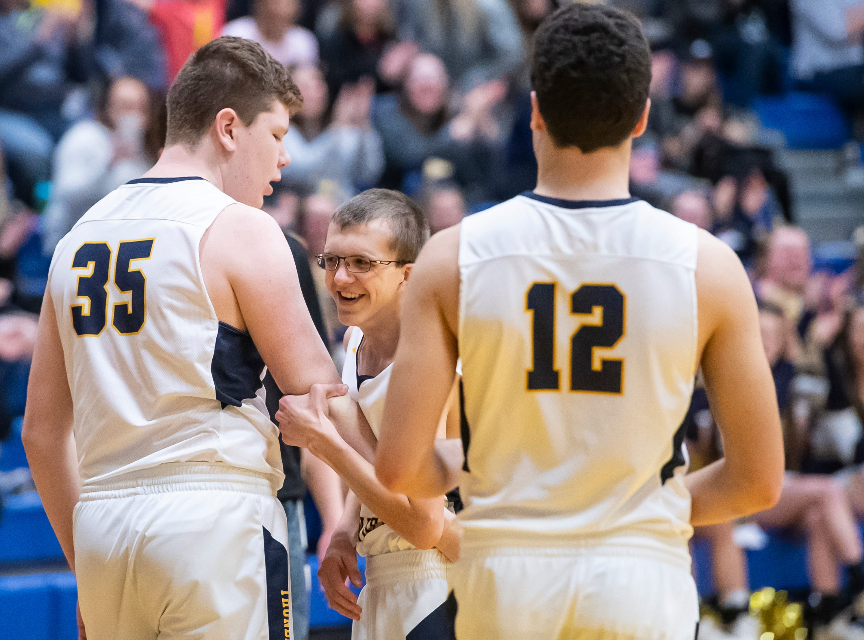 Littlestown's Ben Blankenship, center, is congratulated by his teammates after he  scored the first points of the game against Biglerville Tuesday, February 5, 2019. The Bolts won 54-46 on senior night.