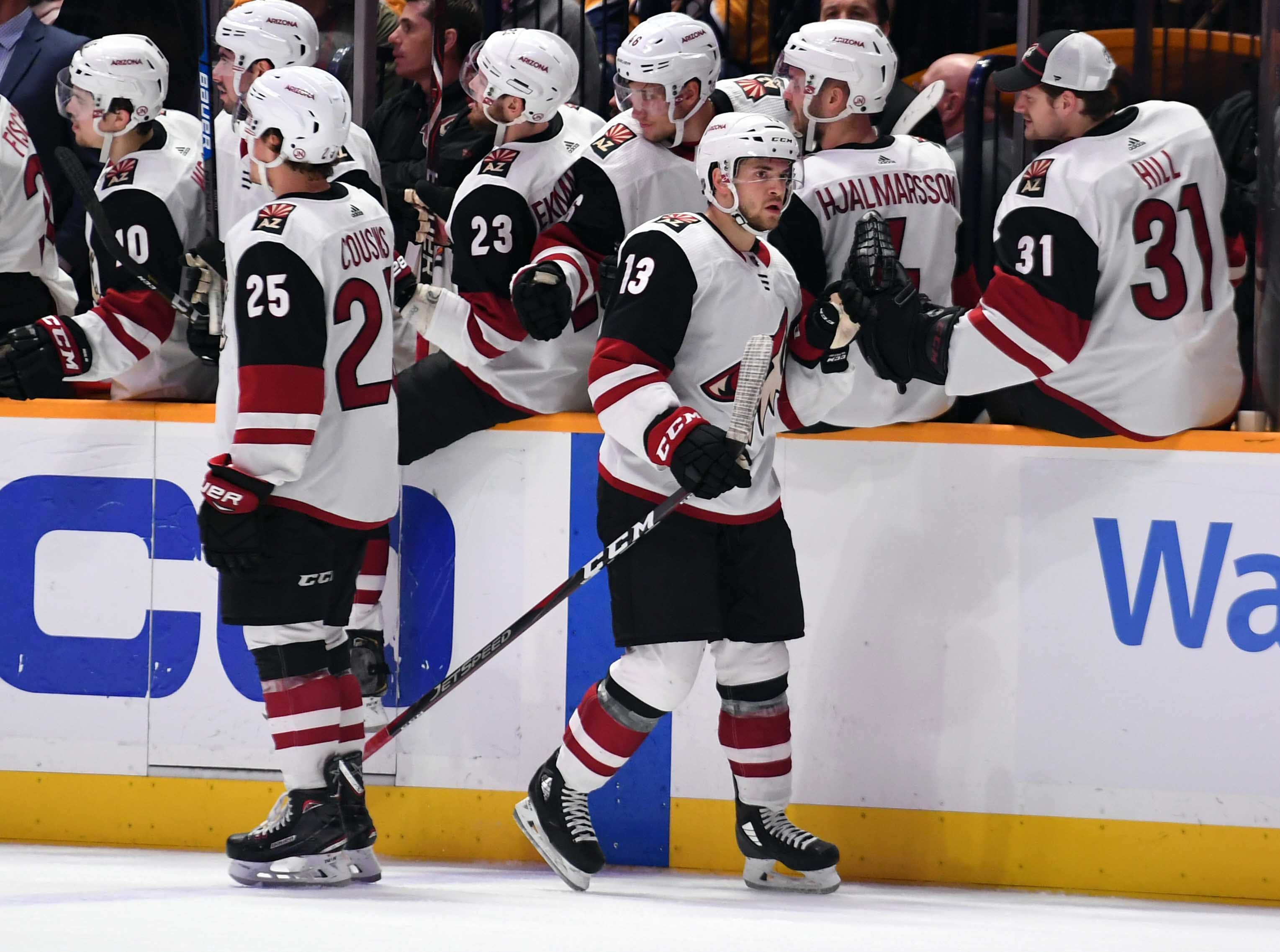 Feb 5, 2019; Nashville, TN, USA; Arizona Coyotes center Vinnie Hinostroza (13) is congratulated by teammates after a goal during the first period against the Nashville Predators at Bridgestone Arena. Mandatory Credit: Christopher Hanewinckel-USA TODAY Sports