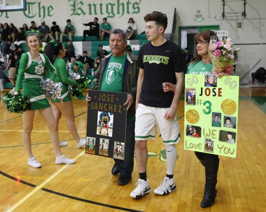 St. Mary's Jose Sanchez is escorted by his grandparents, Javier and Rosa Echerivel, during senior night before playing against Moon Valley in Phoenix Feb. 5, 2019. His grandparents took care of him after both his parents were killed in a car accident.