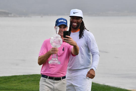 Kevin Streelman and Larry Fitzgerald take a selfie with the trophy after winning the the AT&T Pebble Beach Pro-Am golf tournament.