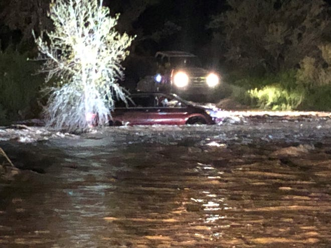 Three people were rescued from a vehicle stranded in a running wash in Cave Creek.