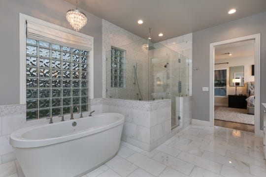 This Phoenix home purchased by Thomas Chaly Jr., and his wife Amanda, features a master bathroom with Carrera marble flooring, a soaking tub and his-and-hers vanities.
