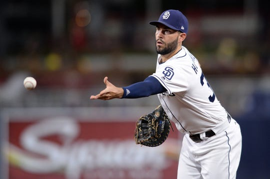 Padres first baseman Eric Hosmer tosses the ball to first base for a force out during a game against the Giants at Petco Park.