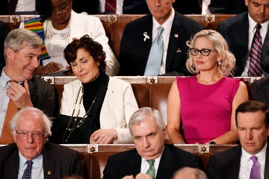 Sen. Kyrsten Sinema (D-Ariz.) listens to President Donald Trump deliver the State of the Union address from the House chamber of the United States Capitol in Washington on Feb. 5, 2019.