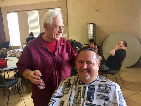 """Tom Laktas hands David a mirror to look at his fresh haircut at the New Hope Community Center in Mesa, an outreach ministry of Broadway Christian Church, where people in need can get help with food and clothing, among other things. David shook Tom's hand. """"I appreciate it,"""" David said."""