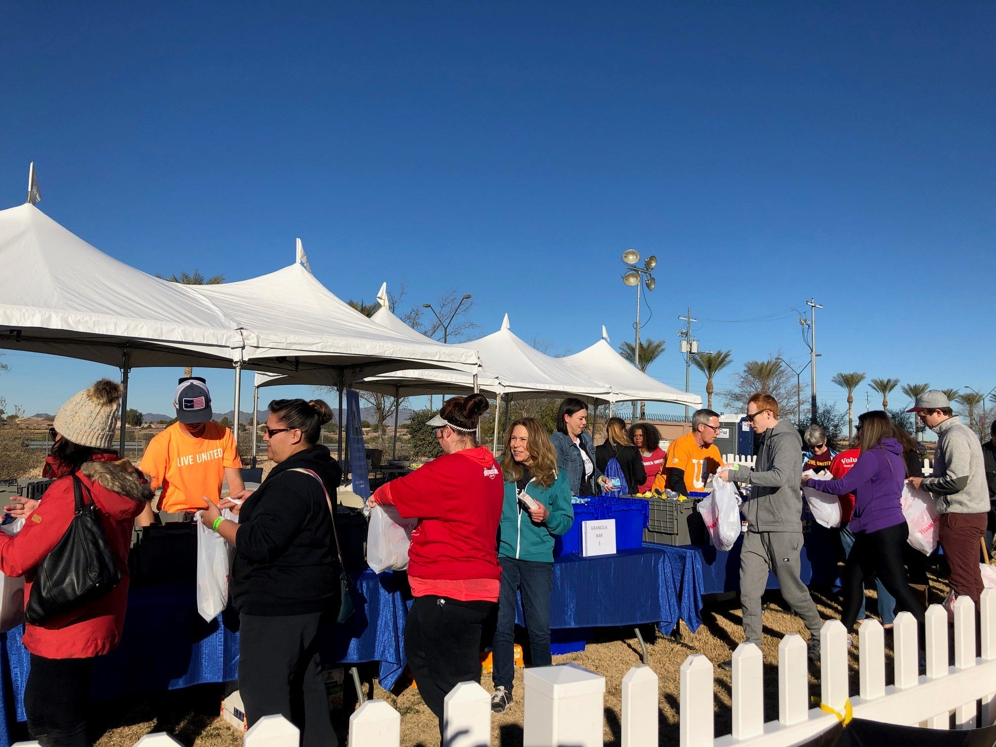 Voluntarios empacan comida para jóvenes en la comunidad.
